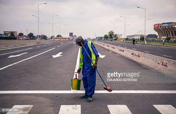 A public cleaner works on a deserted avenue as the Congolese capital Kinshasa was gripped by a strike called 'Villes mortes' on October 19 2016 in a...