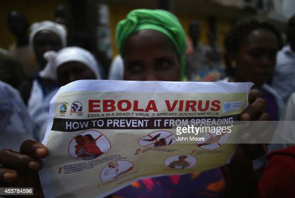 Public health advocates stage street theater to attract people to attend an Ebola awareness and prevention event on August 18 2014 in Monrovia...