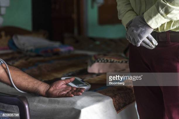 A Public Health Foundation of India worker right takes the blood pressure reading of a patient during a free doortodoor screening program funded by...