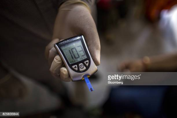 A Public Health Foundation of India worker shows the blood glucose level of a patient during a free doortodoor screening program funded by Eli Lilly...