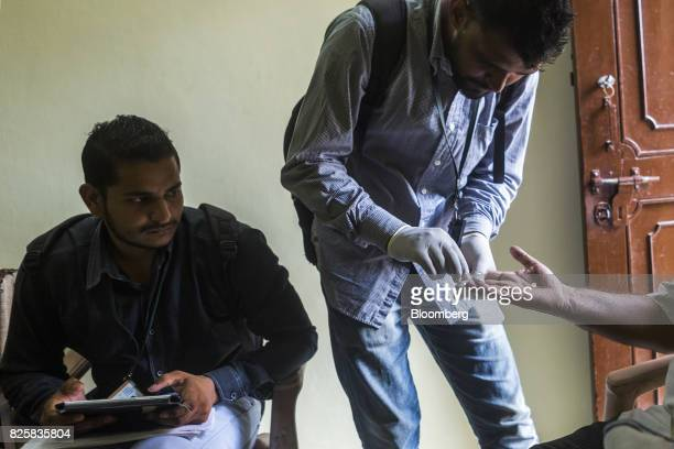 A Public Health Foundation of India worker takes a blood sample from a patient during a free doortodoor screening program funded by Eli Lilly Co at a...