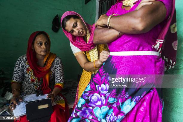 Public Health Foundation of India workers measure the waist of a patient during a free doortodoor screening program funded by Eli Lilly Co at a home...