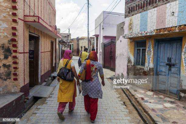 Public Health Foundation of India workers walk through a lane of the farming village of Thana kalan Haryana India on Thursday July 13 2017 Global...
