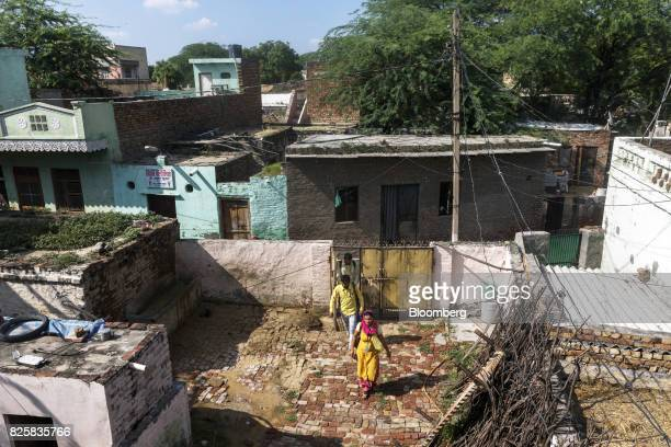 Public Health Foundation of India workers walk through the courtyard of a house in the farming village of Thana kalan Haryana India on Thursday July...