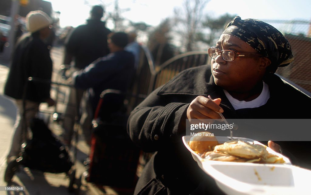 Public housing resident Tiffany Grinnage eats her free donated Thanksgiving meal while waiting in line to collect donated items in the Rockaway neighborhood on November 22, 2012 in the Queens borough of New York City. A number of organizations are providing free Thanksgiving meals for residents of the Rockaways which was hard hit by Superstorm Sandy.
