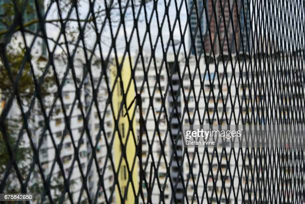 A public housing tower block is seen through a rusty old chainlink fence