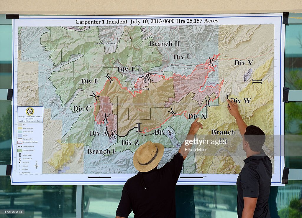 Public information officer James Stone (L) goes over a briefing map for the Carpenter 1 fire with newspaper reporter Colton Lochhead at the incident command post at Centennial High School on July 10, 2013 in Las Vegas, Nevada. More than 25,000 acres have burned since lightning sparked the blaze in Carpenter Canyon on the Pahrump, Nevada side of Mount Charleston on July 1. More than 1,000 firefighters are battling the wildfire which crested the peak of Mount Charleston on July 4, prompting the evacuation of 520 people as it began descending the east side of the mountain, about 35 miles northwest of Las Vegas. The fire is 10% contained and fire officials estimate that they won't have it fully contained until July 19.