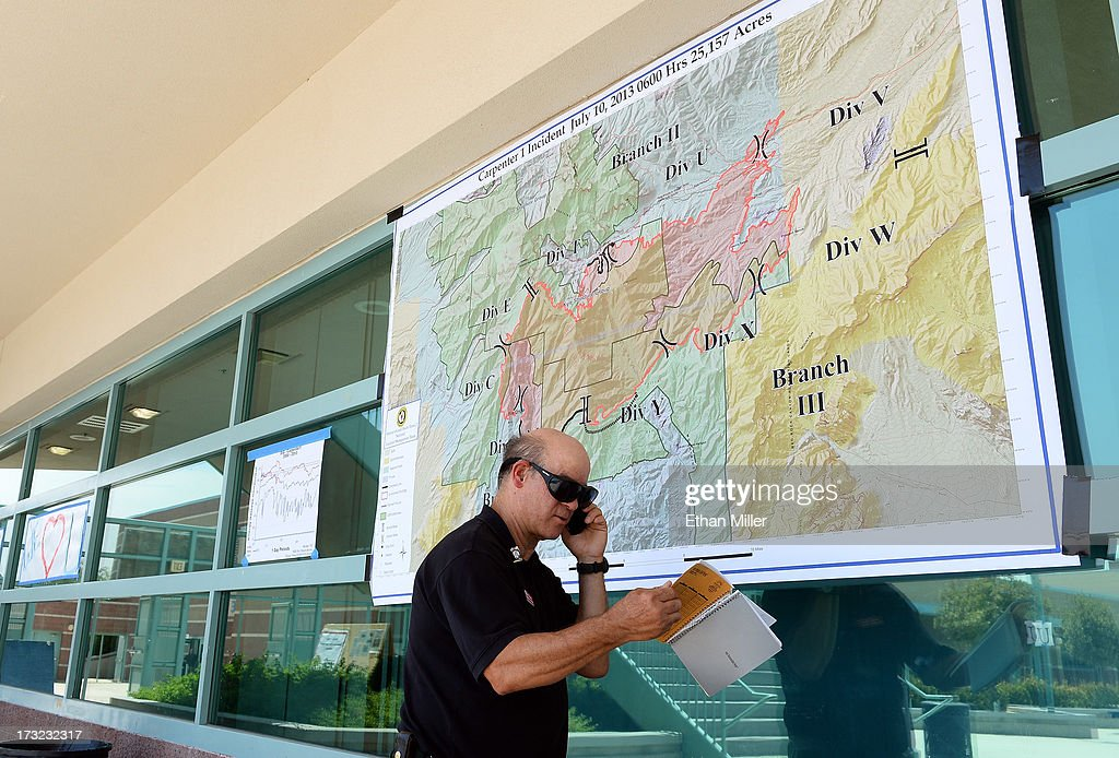 Public information officer James Stone talks on a phone in front of a briefing map for the Carpenter 1 fire at the incident command post at Centennial High School on July 10, 2013 in Las Vegas, Nevada. More than 25,000 acres have burned since lightning sparked the blaze in Carpenter Canyon on the Pahrump, Nevada side of Mount Charleston on July 1. More than 1,000 firefighters are battling the wildfire which crested the peak of Mount Charleston on July 4, prompting the evacuation of 520 people as it began descending the east side of the mountain, about 35 miles northwest of Las Vegas. The fire is 10% contained and fire officials estimate that they won't have it fully contained until July 19.