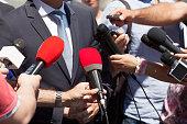 Press interview. Broadcast journalism. Microphones.