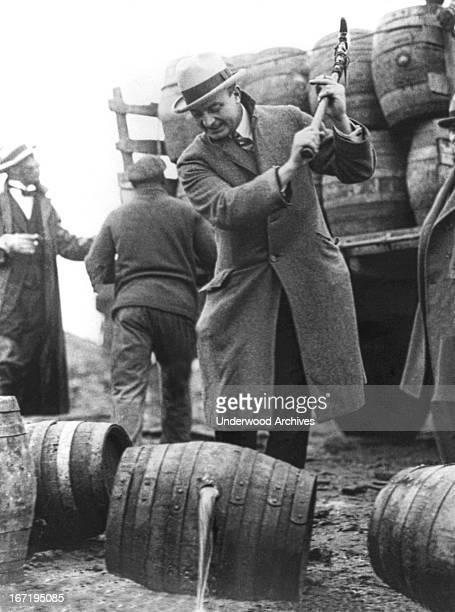Public Safety Director Smedley Butler destroying barrels of beer with a pick axe during Prohibition and letting it run into the Schuylkill River...