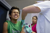 Public school student Julio Valenzuela grimaces as he gets a vaccination at a free immunization clinic for students before the start of the school...