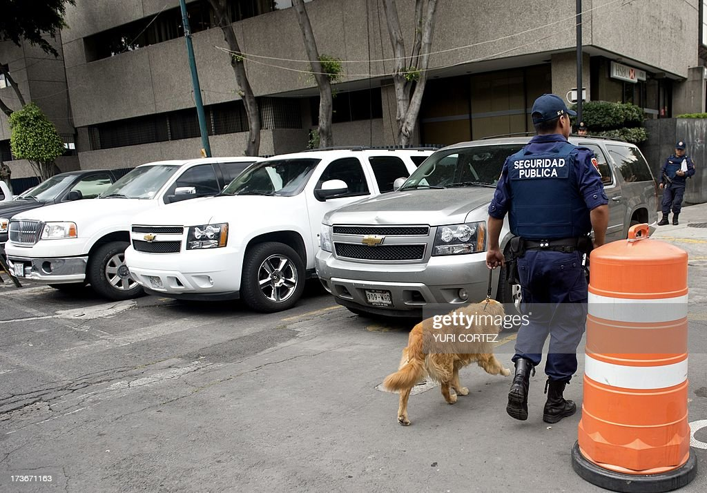 A Public Security member patrols with a sniffer dog the surroundings of the Deputy Attorney Specialized in Investigation of Organized Crime (SEIDO) headquarters, where the alleged maximun leader of drugs Mexican cartel 'Los Zetas' Miguel Angel Trevino Morales, aka 'Z 40', remains under investigation, in Mexico City on July 16, 2013. Trevino's arrest early Monday by Mexican Navy near Nuevo Laredo (Tamaulipas, northeast), bordering the United States, is the most significant blow against drug trafficking by Enrique Pena Nieto government who took office last December. AFP PHOTO / Yuri CORTEZ