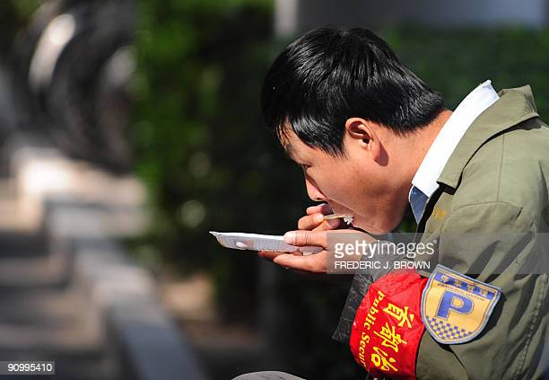 A public security volunteer wearing the ubiquitous red armband eat his lunch in Beijing on September 21 2009 China approaches the October 1 60th...