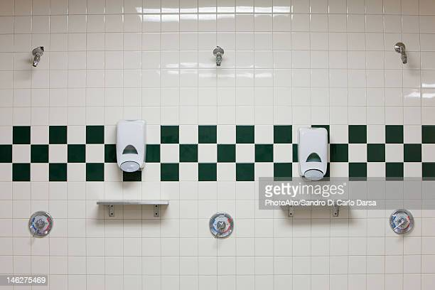 Public shower room with soap dispensers on wall
