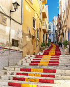 Old town Spanish village with public steps painted in red and yellow, Spanish flag colors.
