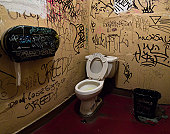 Public toilet with graffiti on wall
