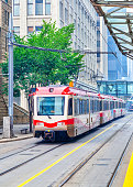 A modern Calgary transit train traveling on the streets of downtown Calgary. Vertical orientation.