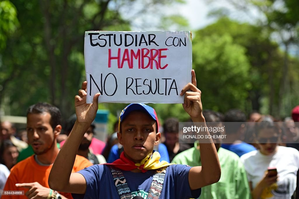 A public university student in Venezuela protesting the policies of the government of President Nicolas Maduro holds a sign reading 'studying when you're hungry doesn't work', in Caracas on May 26, 2016. / AFP / RONALDO