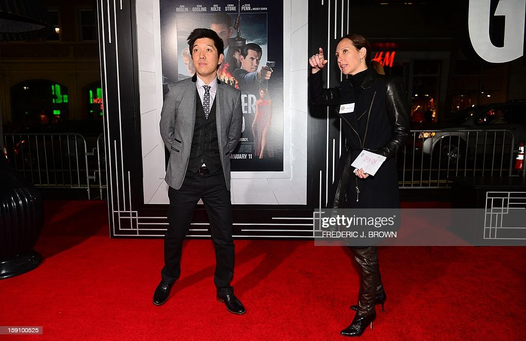 A publicist points towards the cameras for producer of the film Dan Lin, on arrival for the Los Angeles World Premiere of 'Gangster Squad' at Grauman's Chinese Theater on January 7, 2013 in Hollywood,California. The film opens nationwide on January 11. AFP PHOTO / Frederic J. BROWN