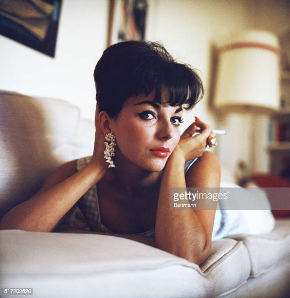 Publicity handout photograph of actress Joan Collins on a couch holding a cigarette near her face ca 1950s
