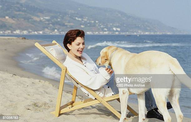Publicity photo for the CBS television drama '2000 Malibu Road' features American actress Drew Barrymore as she sits in a white canvas folding chair...
