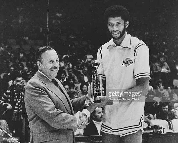 Publicity photo of Kareem AbdulJabbar and Mel Elliot receiving an award at Los Angeles Forum during the Seagrams Seven Crowns of Sports competition...
