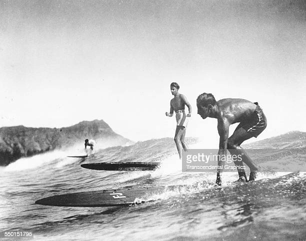 A publicity photograph by the Scotty Bjurstrom Agency featuring surfing action that promotes Hawaiian vacations Chicago Illinois circa 1950