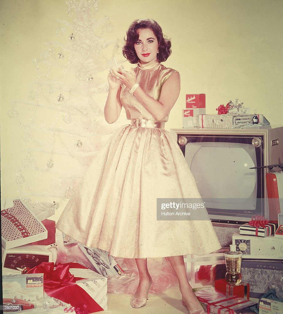 Publicity portrait of British-born actor <a gi-track='captionPersonalityLinkClicked' href=/galleries/search?phrase=Elizabeth+Taylor&family=editorial&specificpeople=69995 ng-click='$event.stopPropagation()'>Elizabeth Taylor</a> in a yellow dress as she stands in front of an artificial Christmas tree amidst a pile of opened presents, including a television set, clothing, and a radio, circa 1950s