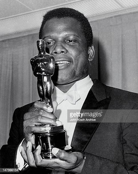 Publicity still of Academy Award winning actor Sidney Poitier holding the Oscar for his role in 'Lilies of the Field' 1964