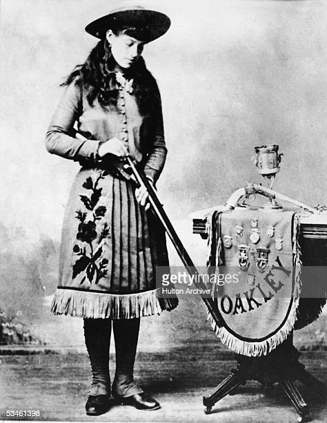 Publicity still of American sharpshooter Annie Oakley as she loads a shotgun near a table display of adorned with various marksmanship medals late...