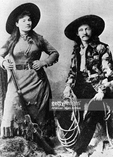Publicity still of American sharpshooter Annie Oakley poses with one knee on a haybale and a shotgun on her hand while Texas Bill Shufflebottom sits...