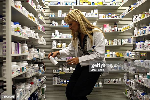 Roxana Selagea a Publix Supermarket pharmacy manager retrieves a bottle of antibiotics from the shelf August 7 2007 in Miami Florida Publix has...