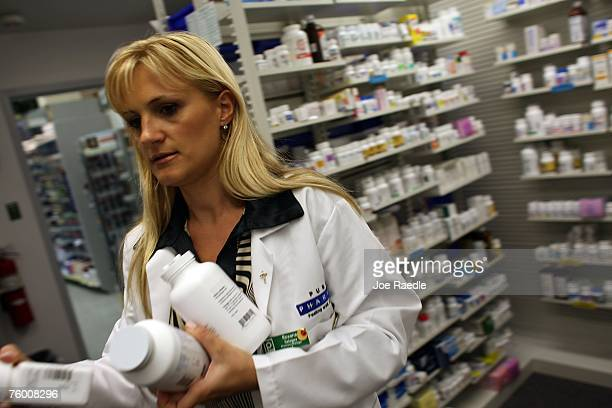 Roxana Selagea a Publix Supermarket pharmacy manager retrieves bottles of antibiotics from the shelf August 7 2007 in Miami Florida Publix has...