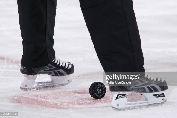 A puck sits on the ice between the skates of the referee during the NHL game between the Calgary Flames and the Ottawa Senators at Scotiabank Place...