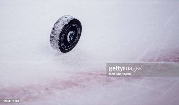 A puck sits on the ice during a stop in play during a NHL hockey game between the Vancouver Canucks and the Edmonton Oilers on October 07 at Rogers...