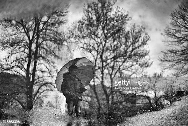 puddle reflection of a boy holding umbrella and trees