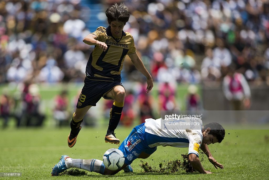 Puebla's Diego Eduardo de Buen (R) falls while disputing the ball with Pumas's Carlos Emilio Orrantia (L) during their Mexican Apertura 2013 tournament football match in Puebla, Mexico on July 21, 2013. The match ended 1-1.