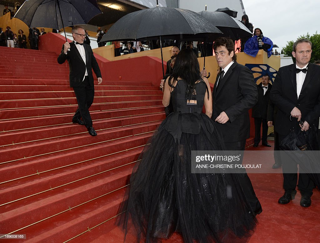 Puerto Rican actor Benicio Del Toro (2ndR) walks on the red carpet under pouring rain on May 18, 2013 as he arrives the screening of the film 'Jimmy P. Psychotherapy of a Plains Indian' presented in Competition at the 66th edition of the Cannes Film Festival in Cannes. Cannes, one of the world's top film festivals, opened on May 15 and will climax on May 26 with awards selected by a jury headed this year by Hollywood legend Steven Spielberg.