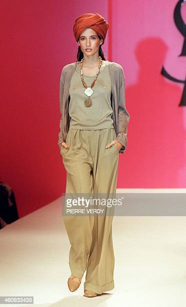Puerto Rican model Astrid Munoz presents a cardigan over a sheer top and long baggy pants by Yves Saint Laurent for his Spring/Summer '99 readytowear...