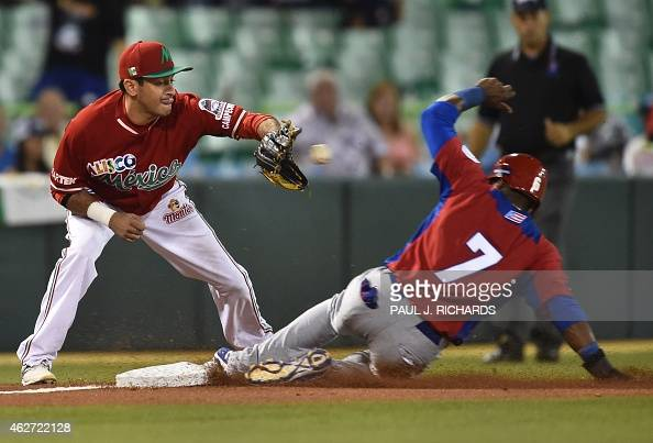 Puerto Rican National baseball team player beats the throw to Mexican National team third baseman Oscar Robles in the second inning of the San Juan...