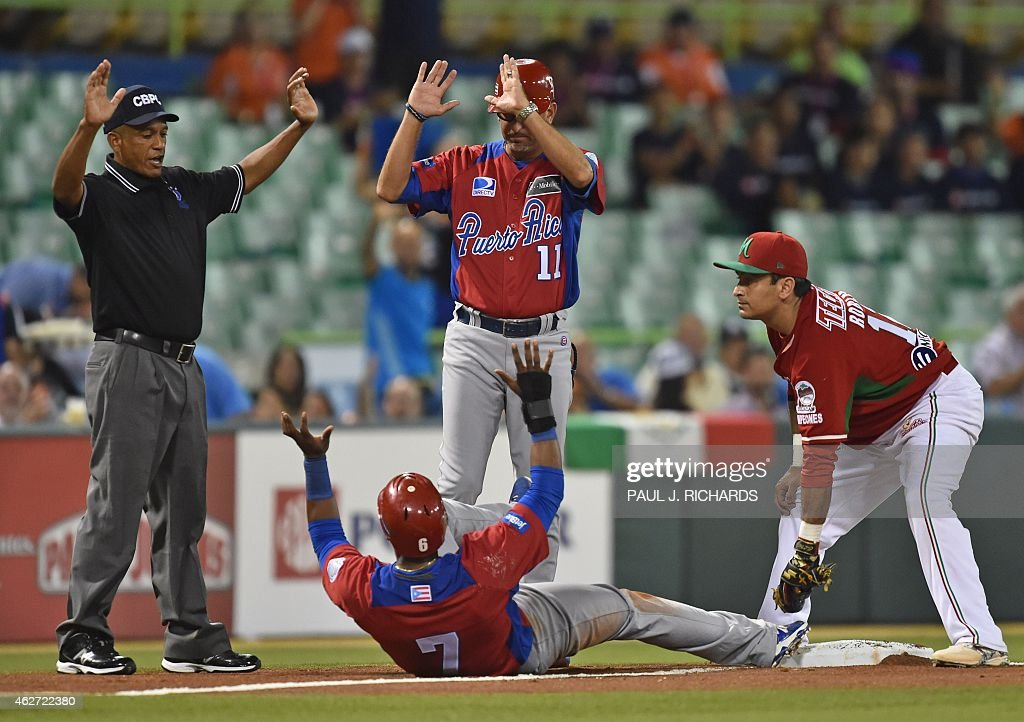 Puerto Rican National baseball team player (#7) beats the throw to Mexican National third baseman <a gi-track='captionPersonalityLinkClicked' href=/galleries/search?phrase=Oscar+Robles&family=editorial&specificpeople=240426 ng-click='$event.stopPropagation()'>Oscar Robles</a> (R) before umpire Domingo Polanco (L) and the Puerto Rican third base coach Jose David Flores (#11) in the second inning of the San Juan Serie Del Caribe February 3, 2015 in San Juan, Puerto Rico.