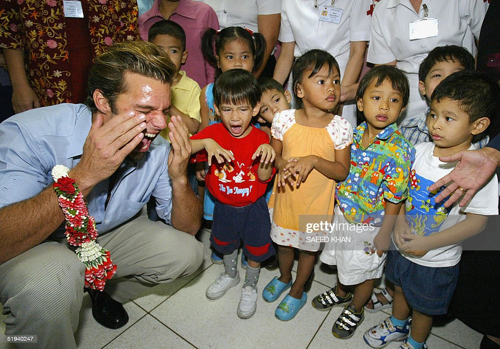 Puerto Rican singer Ricky Martin (L) having fun with Thai orphan children at a Thai Red Cross Society in Bangkok, 12 January 2005. Martin, who has lent his celebrity to help the United Nations Children's Fund, said he would visit areas in Thailand devastated by the giant waves and make a donation to help Thai orphans through his foundation. AFPPHOTO/Saeed KHAN