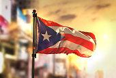 Puerto Rico Flag Against City Blurred Background At Sunrise Backlight