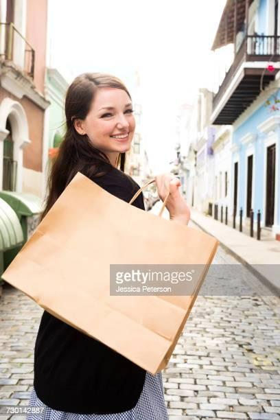 Puerto Rico, San Juan, Woman with shopping bag walking city streets