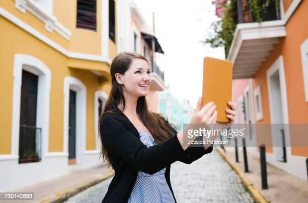 Puerto Rico, San Juan, Woman with tablet doing selfie on city street