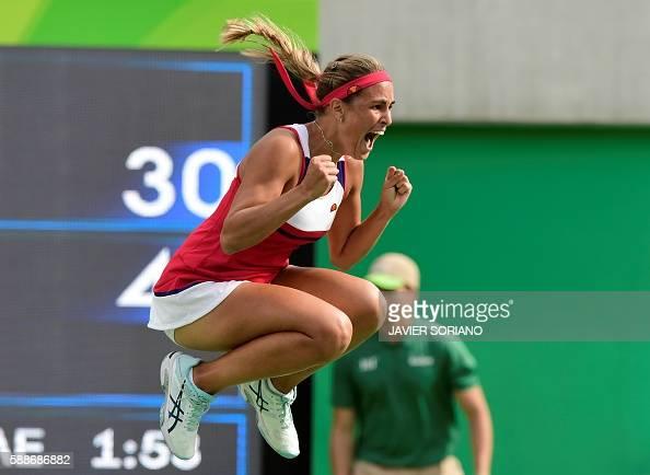 TOPSHOT Puerto Rico's Monica Puig celebrates after winning her women's singles semifinals tennis match against Czech Republic's Petra Kvitova at the...