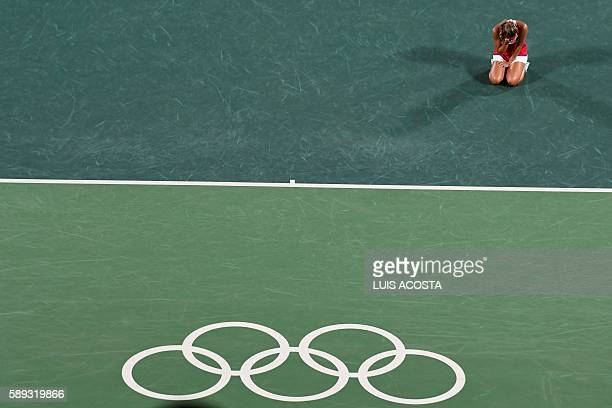 TOPSHOT Puerto Rico's Monica Puig reacts after winning her women's singles final tennis match against Germany's Angelique Kerber at the Olympic...