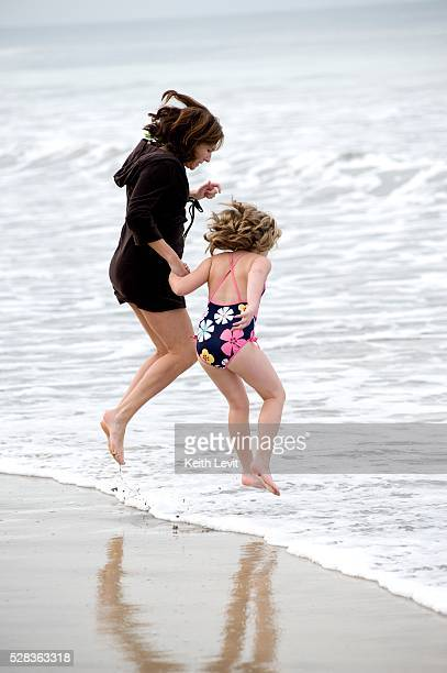 Puerto Vallarta, Mexico; Mother and daughter jumping in the water