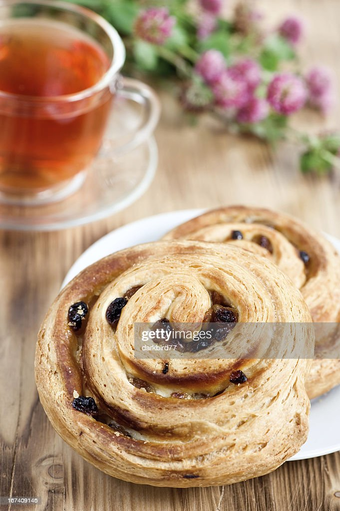 Puff buns with raisin and cup of tea : Stock Photo