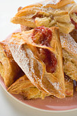 Puff pastries with jam filling on plate, close up